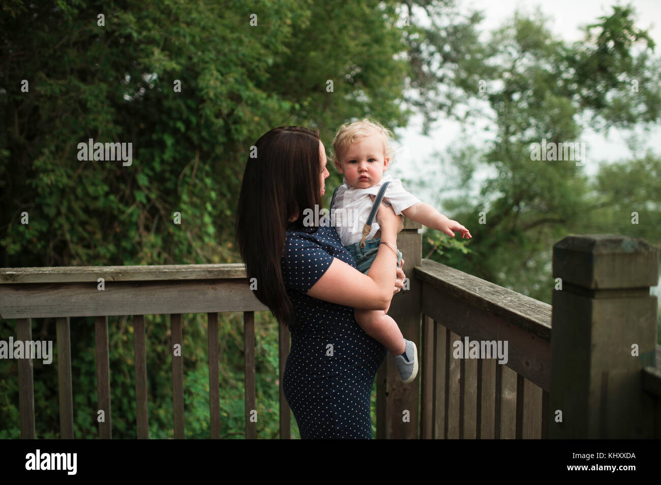 Pregnant woman carrying toddler son on balcony - Stock Image