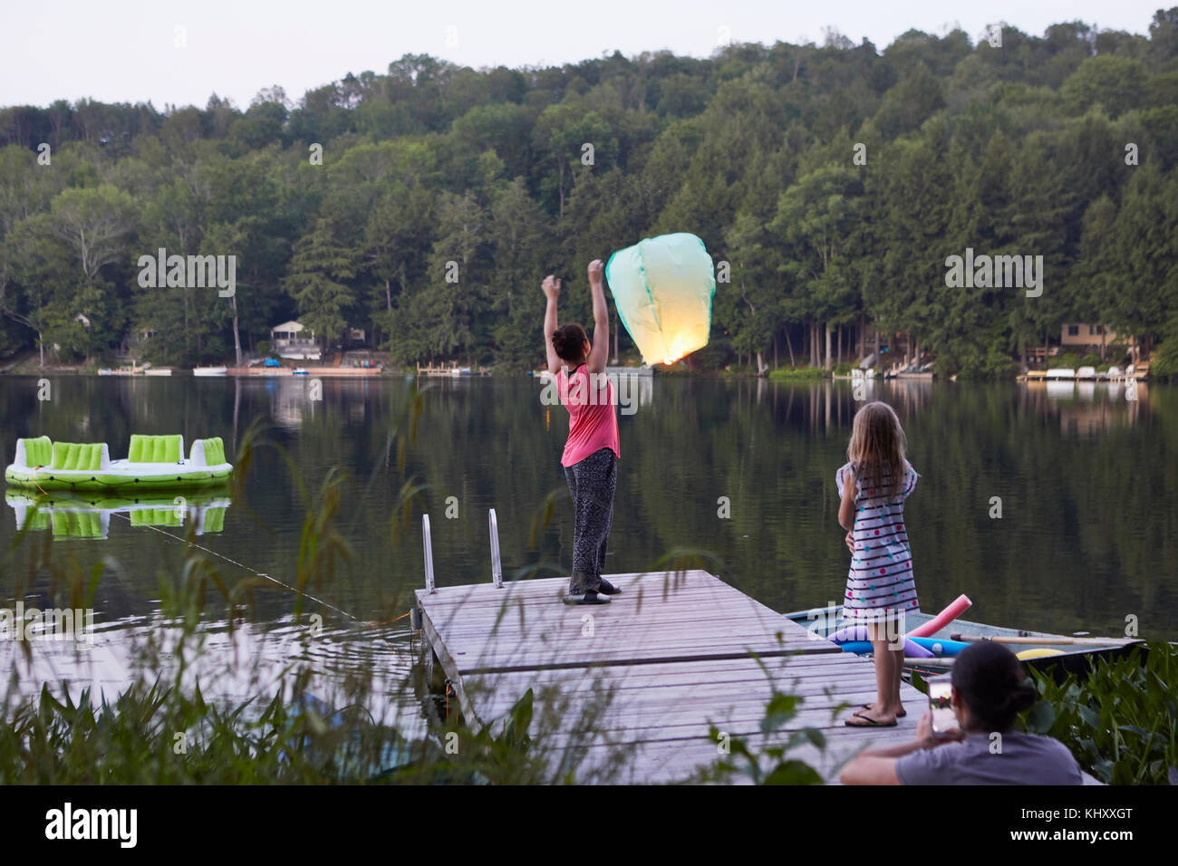 Girl standing on jetty releasing sky lantern, young girl watching, woman photographing event using smartphone Stock Photo