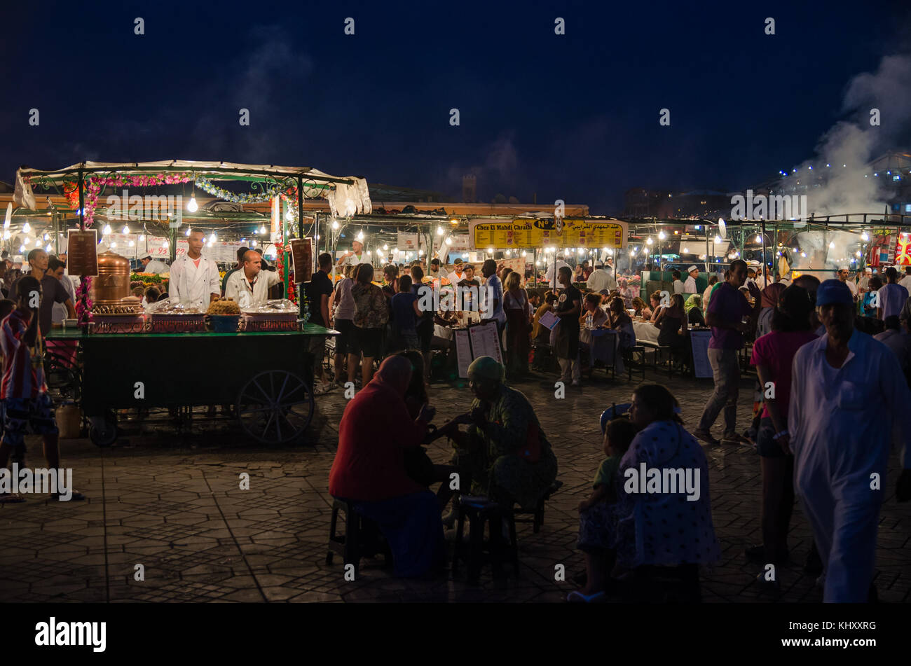 Marrakesh, Morocco - September 05 2013: Food stands with smoke and light on famous Jamaa el Fna square in evening - Stock Image