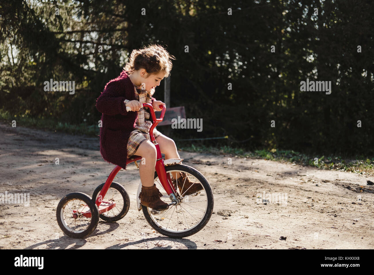 Girl on tricycle - Stock Image