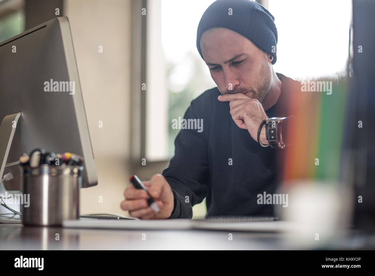 Young male designer contemplating at home desk - Stock Image
