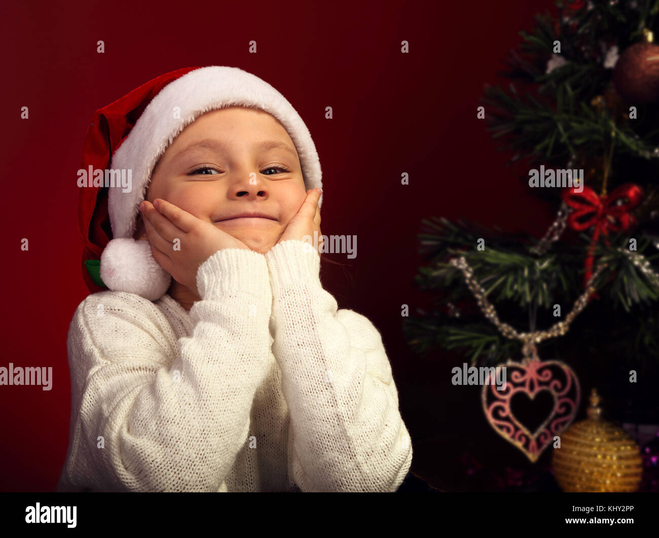 Cute happy smiling kid girl in fur santa claus hat near the Christmas holiday tree thinking about the gift with - Stock Image