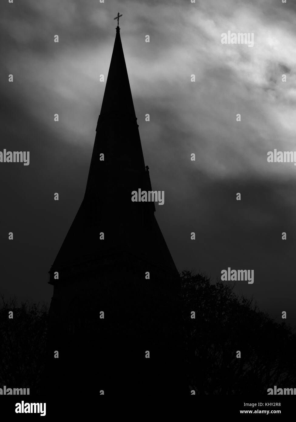Silhouette of a Church Spire against a Dark Cloudy Sky - Stock Image