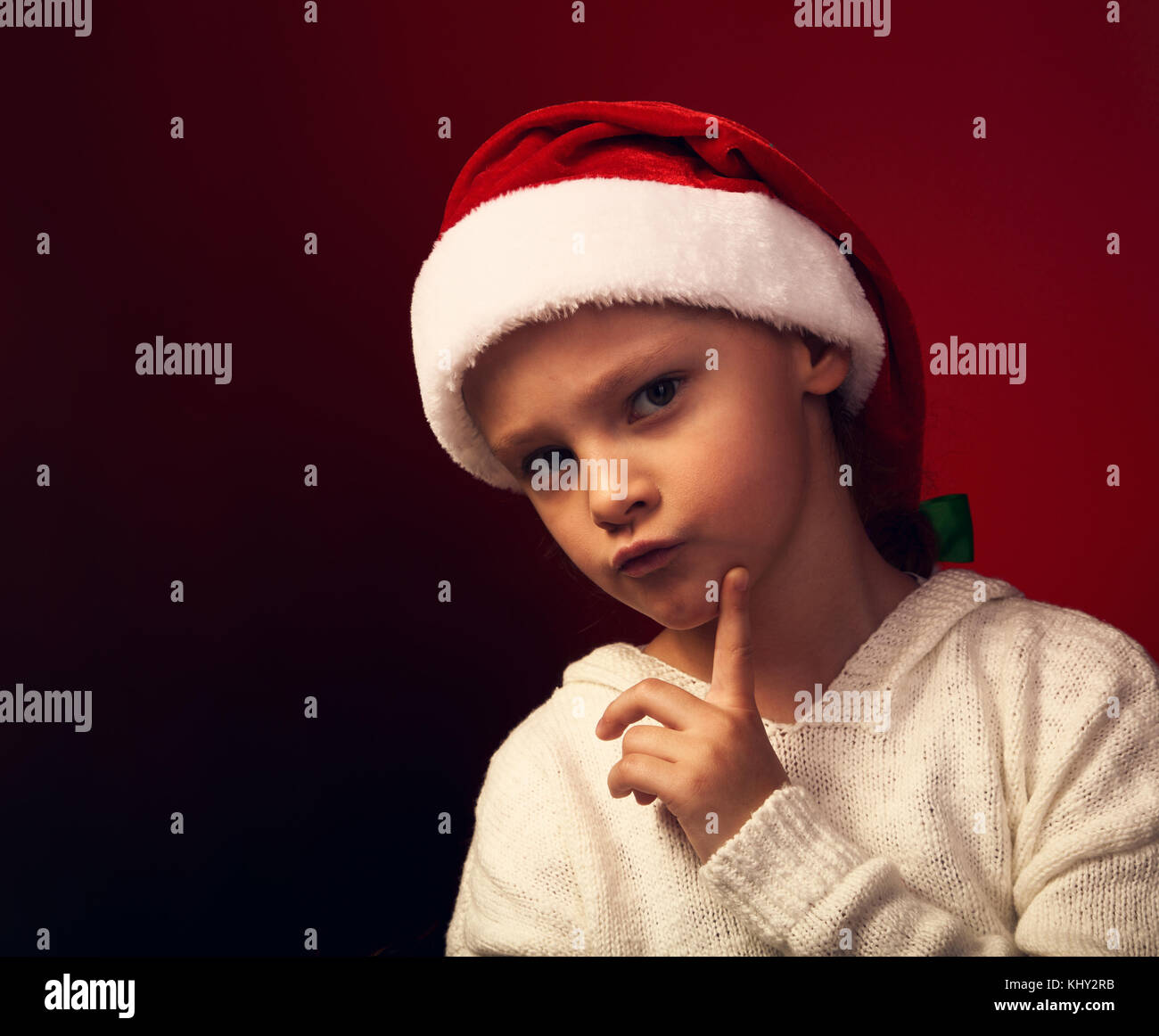 Cute angry girl in fur santa claus hat near the Christmas thinking about the gift with grimacing face and looking - Stock Image