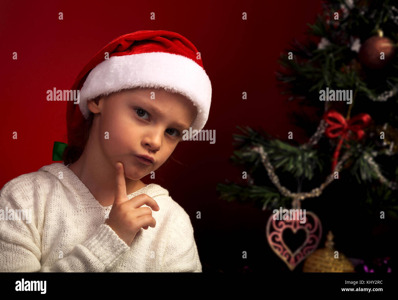 Cute angry girl in fur santa claus hat near the Christmas holiday tree thinking about the gift with grimacing face - Stock Image