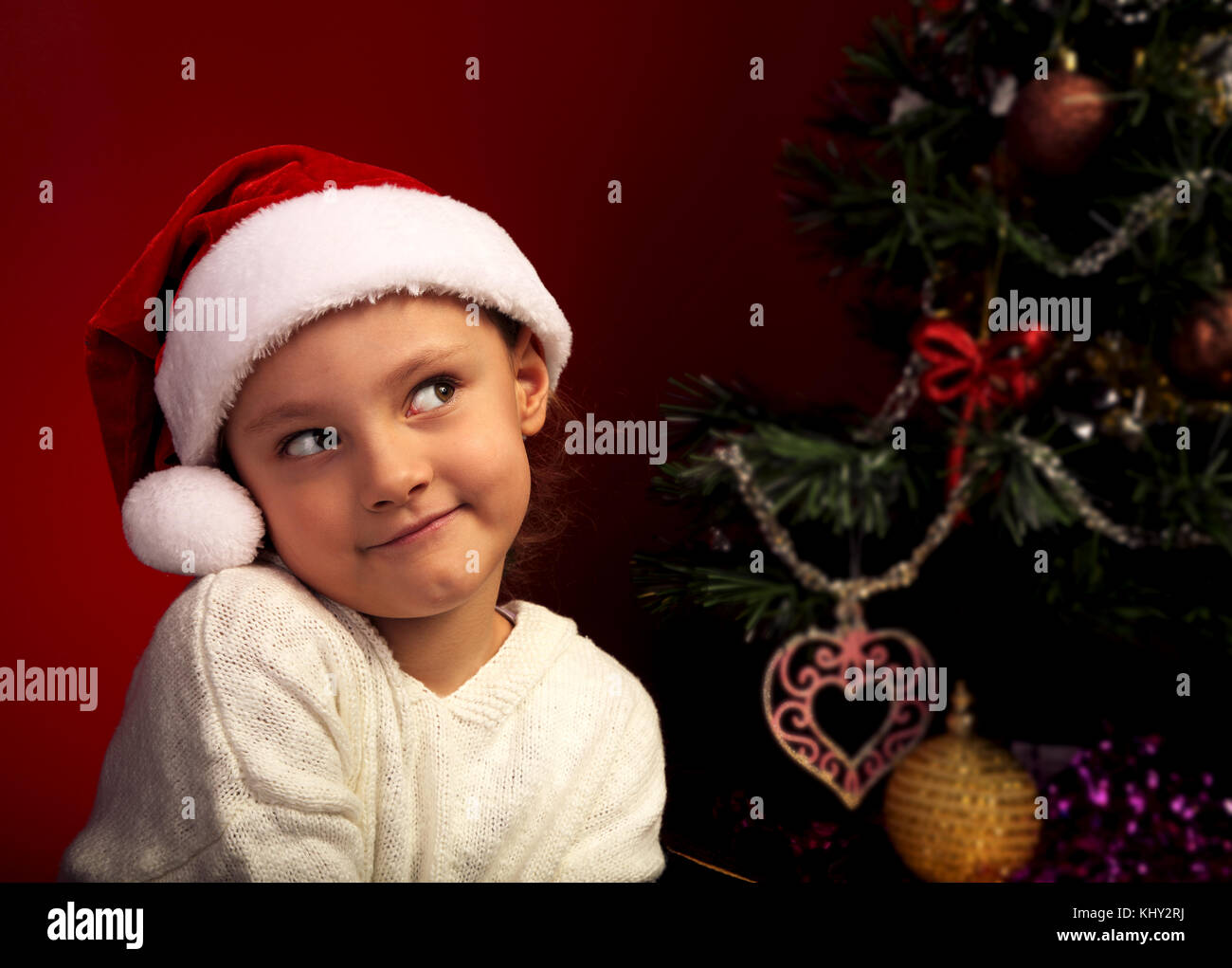 Cute happy smiling girl in fur santa claus hat near the Christmas holiday tree thinking about the gift with grimacing - Stock Image