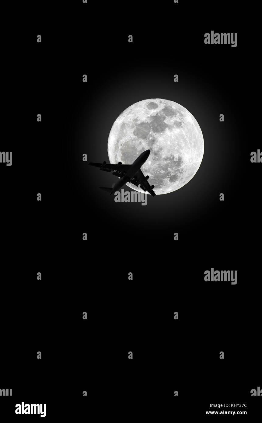 jumbo jet aircraft crossing moon - Stock Image