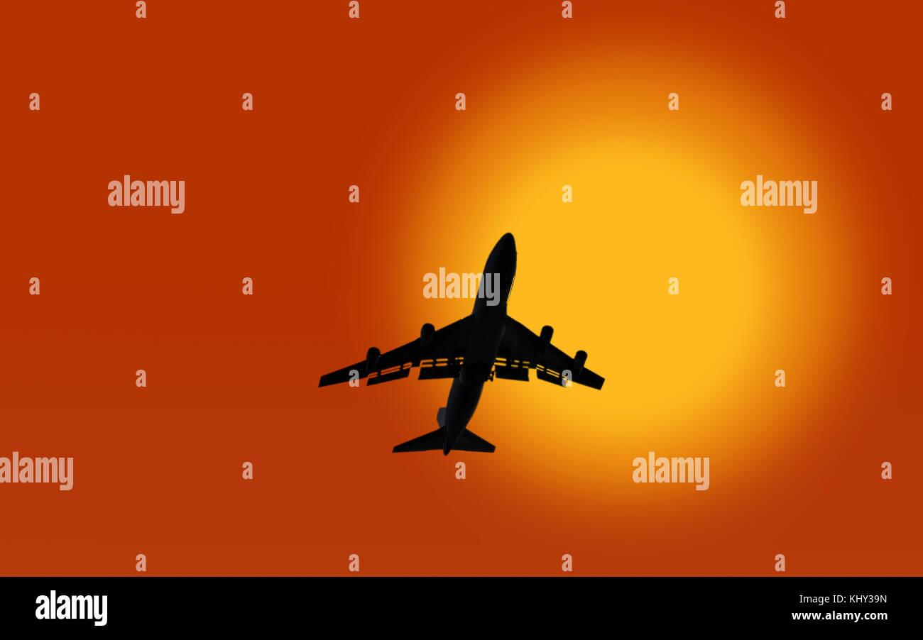 jumbo jet aeroplane crossing sun - Stock Image