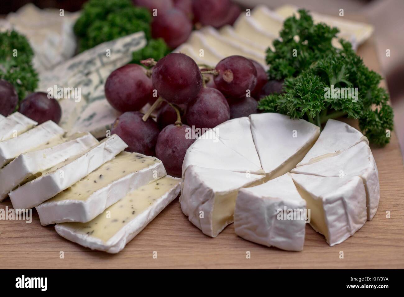 Cheese board: Camembert with herbs decorated with grapes and parsley - Stock Image