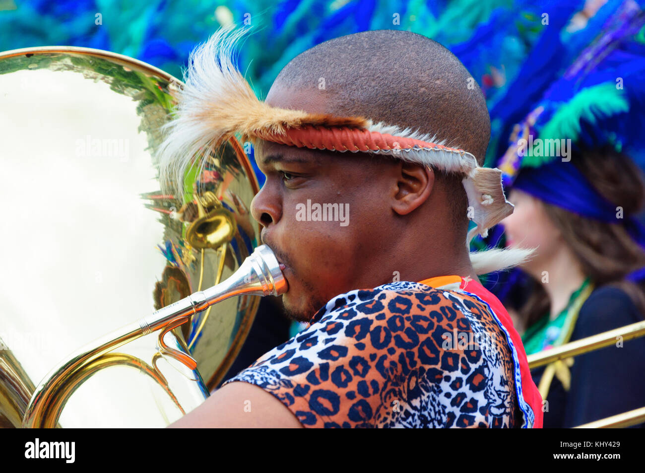 Male musician wearing feathered headgear and playing a tuba in the Carnival of The Edinburgh Jazz and Blues Festival - Stock Image