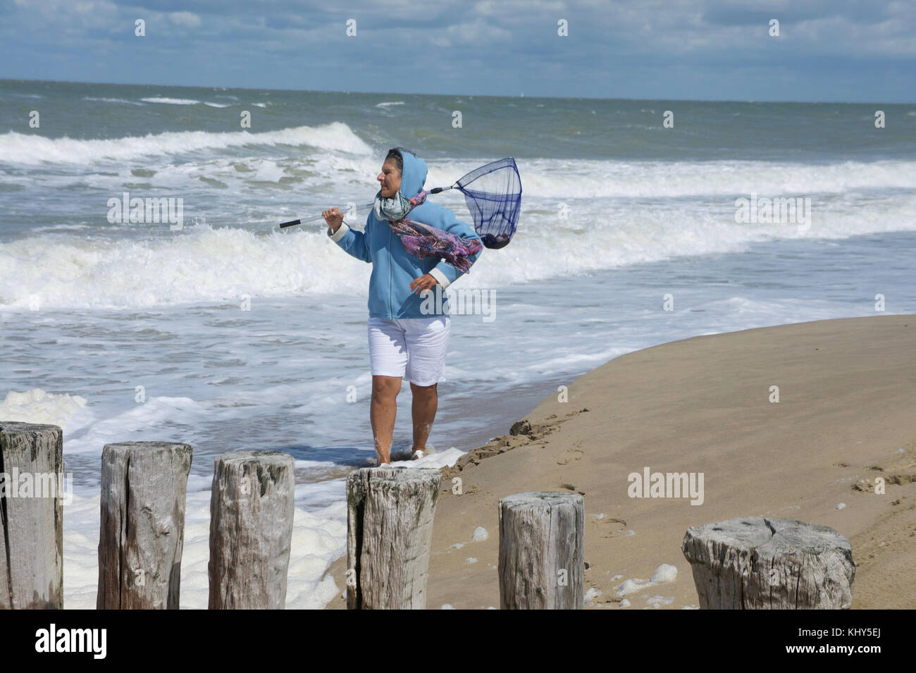 Portrait of a german woman wearing a scarf and cap on the beach during a wind walk. Woman carries a net over her - Stock Image