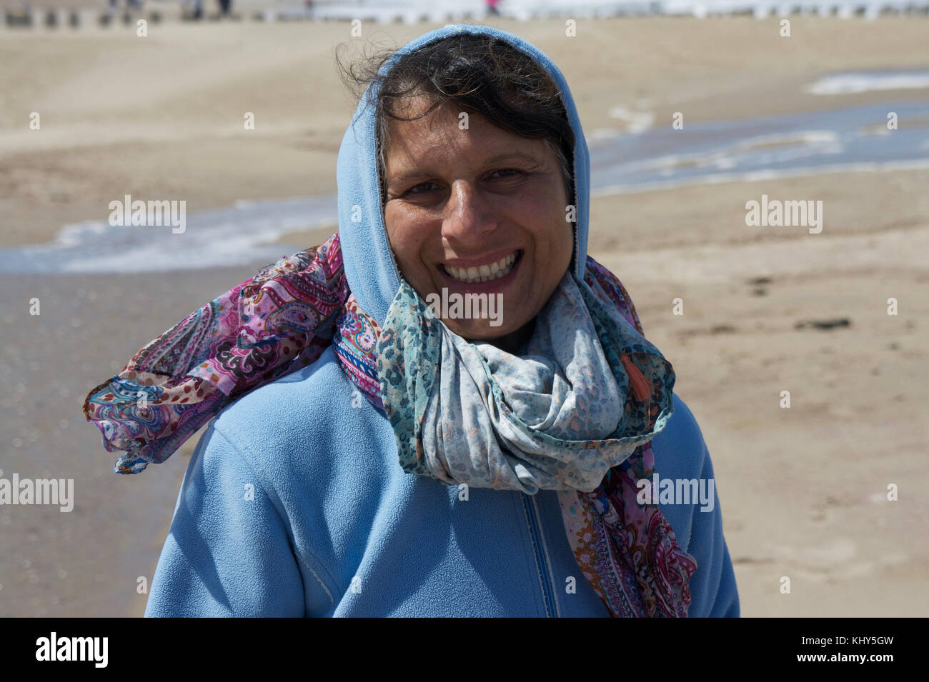 Portrait of a german woman wearing a scarf and cap on the beach during a wind walk. Woman laughing at the photographer. - Stock Image