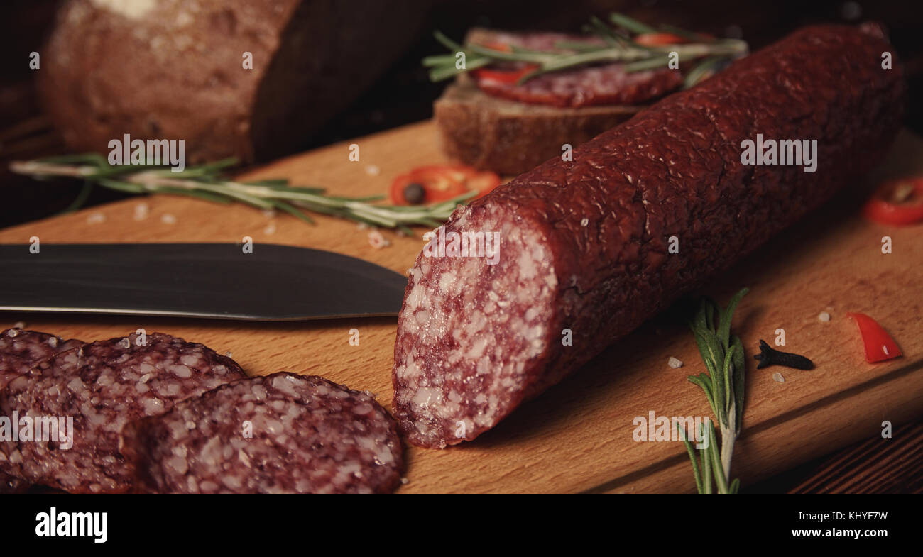 Smoked sausage on a wooden board - Stock Image