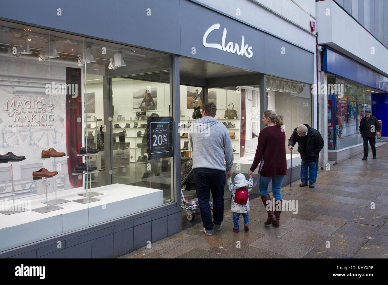 f197c072 Preston, Lancashire, UK Shoppers passing Clarks shoe store sale, shop front  with Summer