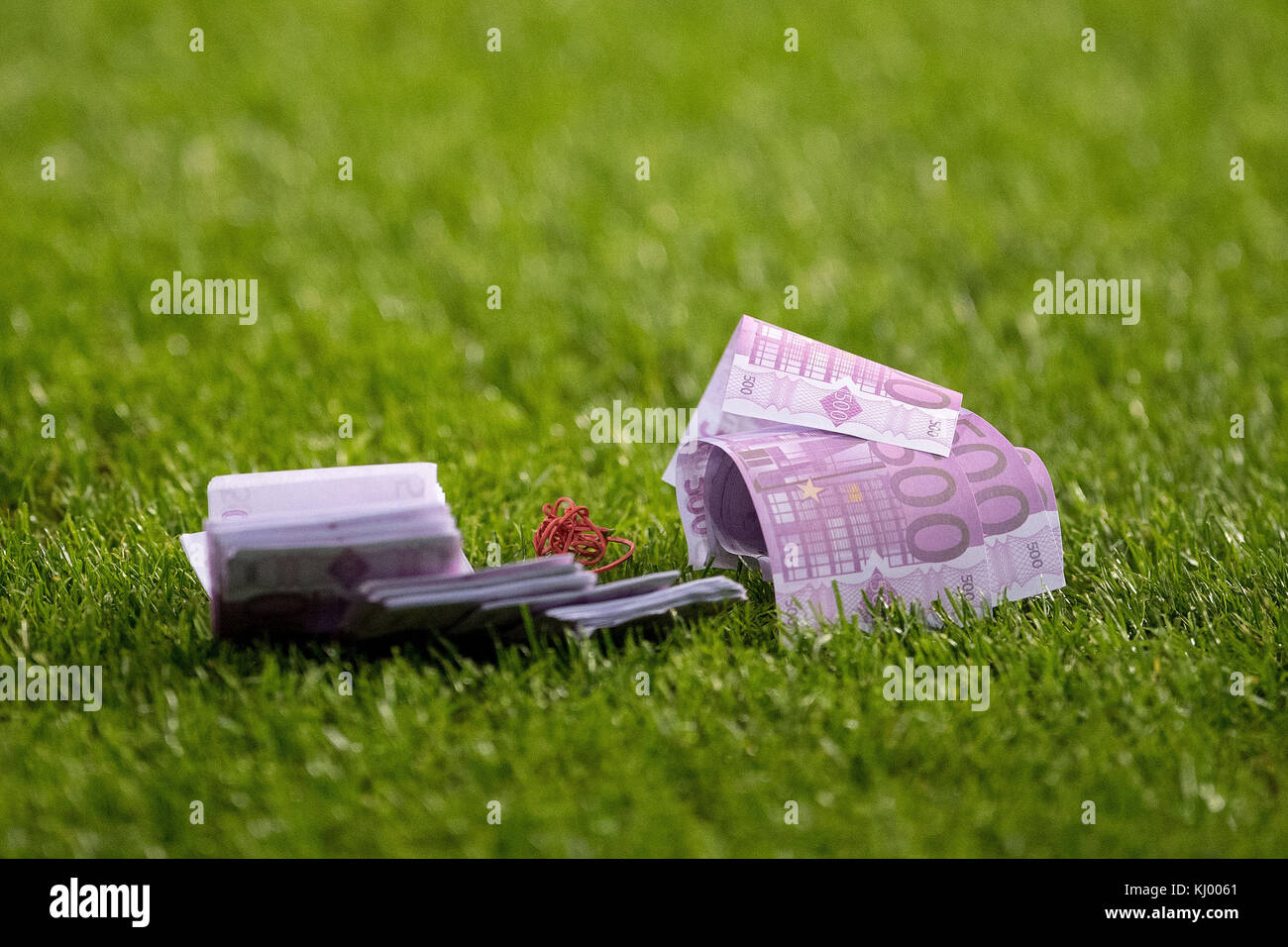 Play money, which was thrown on the pitch by FC Bayern Munich fans, lies on the grass during the Champions League - Stock Image