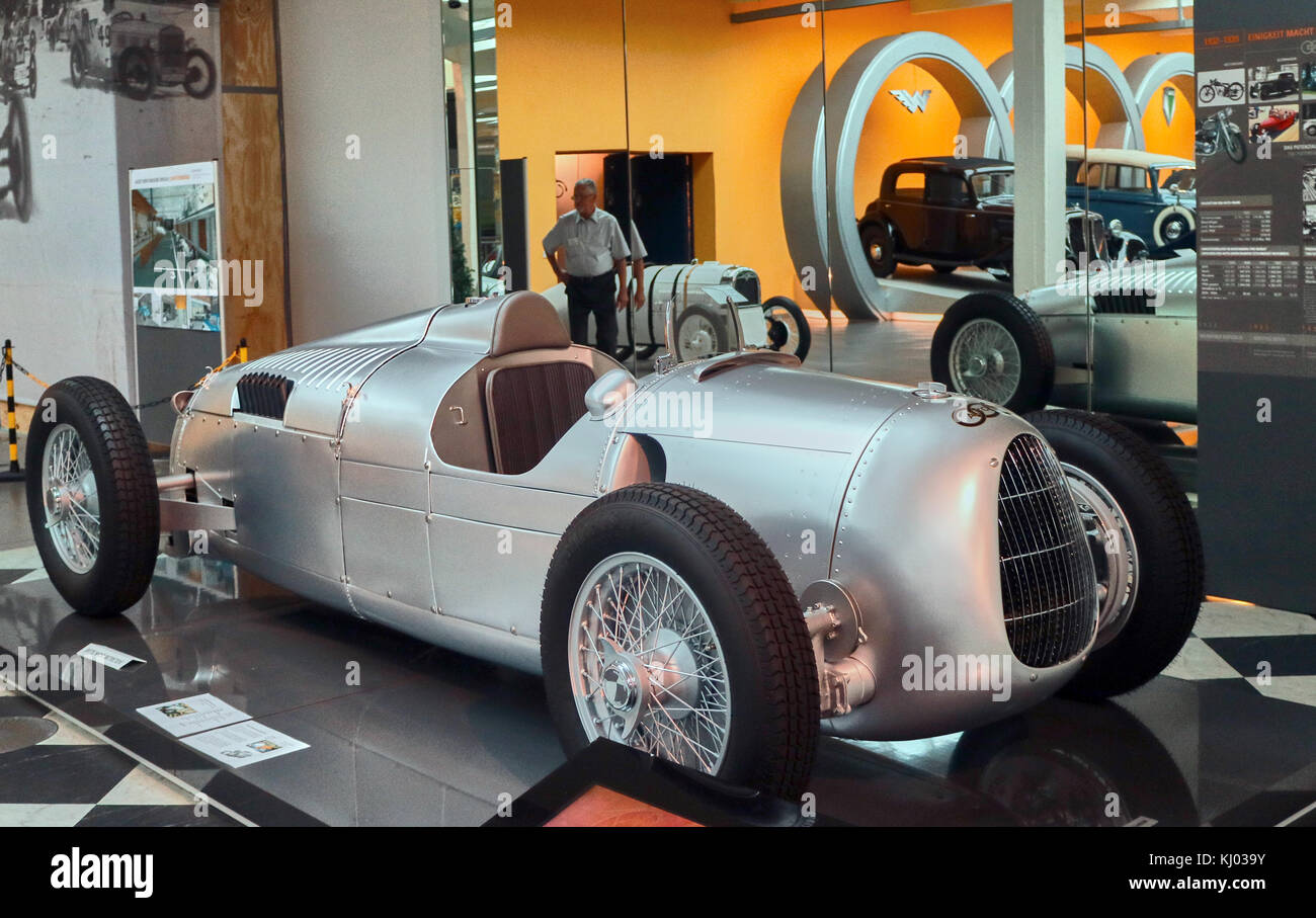 """Europe, Germany, Saxony, Zwickau city, The August Horch Museum, old Bolide Auto Union Flèche d'Argent type C, 1934-1939 Le Mans,  Ferdinand Porsche, then employed by Auto Union, is the first to look into this new project. Porsche developed an imposing """"bolide"""" for the era: the chassis is entirely new, using aluminum beams in which the cooling water passes, the suspension uses A torsion bar, the gearbox is greased under pressure and the engine is a compressor V16. The presence of only three camshafts and 16 valves controlled by rods and tumblers from a common shaft testifies Stock Photo"""