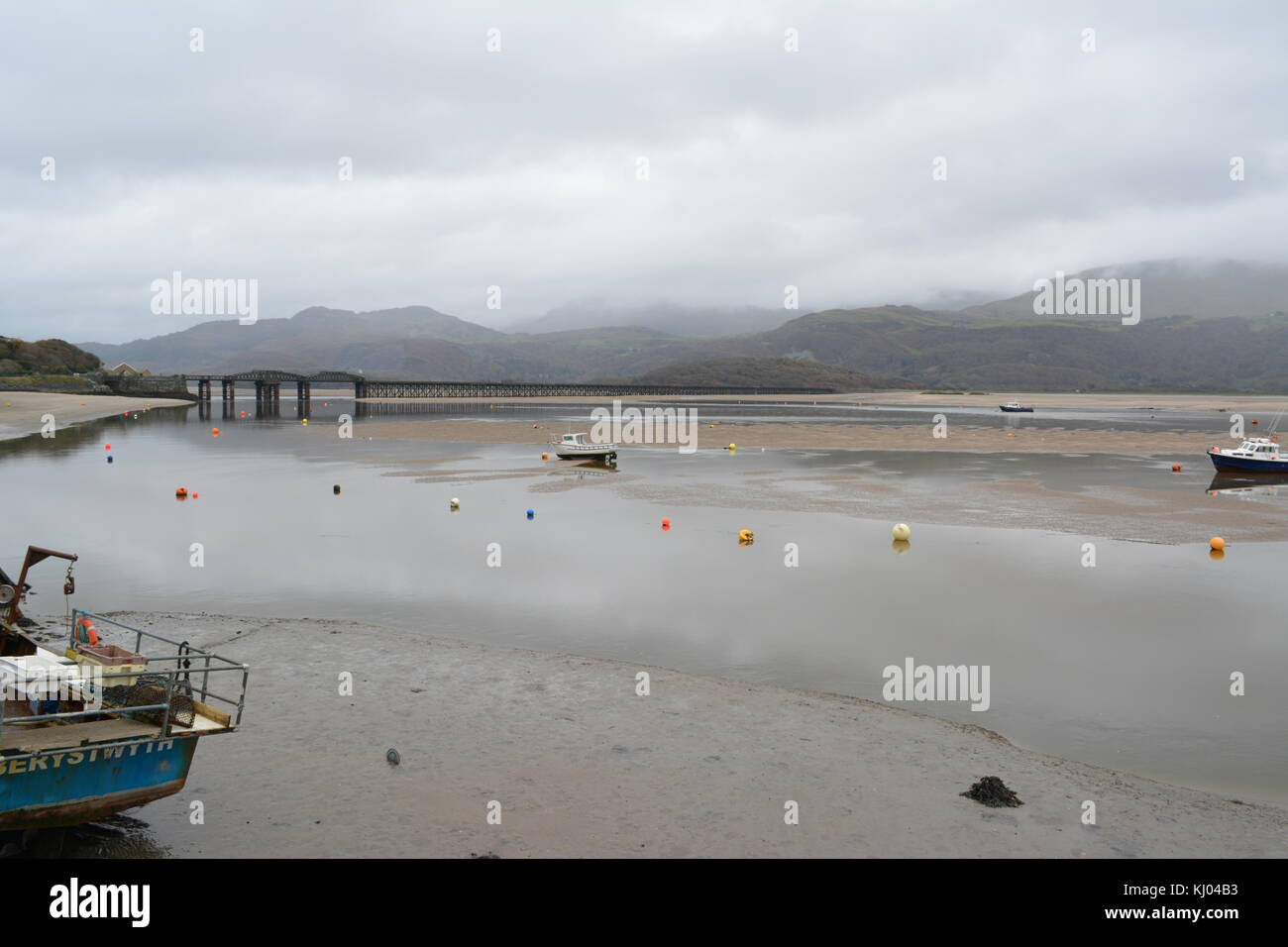 Tide out on the Afon Mawddach estuary on an overcast cloudy day looking from the harbour towards Barmouth railway Stock Photo