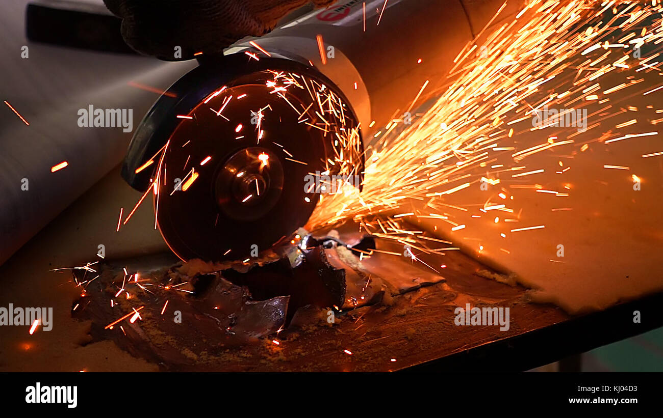 Cutting metal with disc grinder with bright sparks - Stock Image