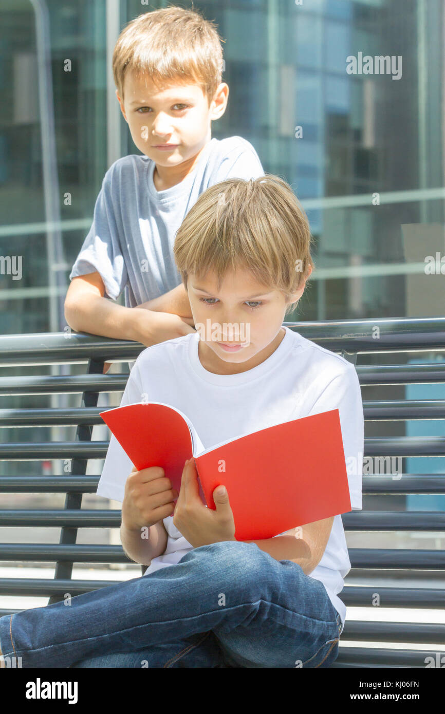 Schoolboys reading books. Kids doing homework outdoors. Back to school concept. - Stock Image