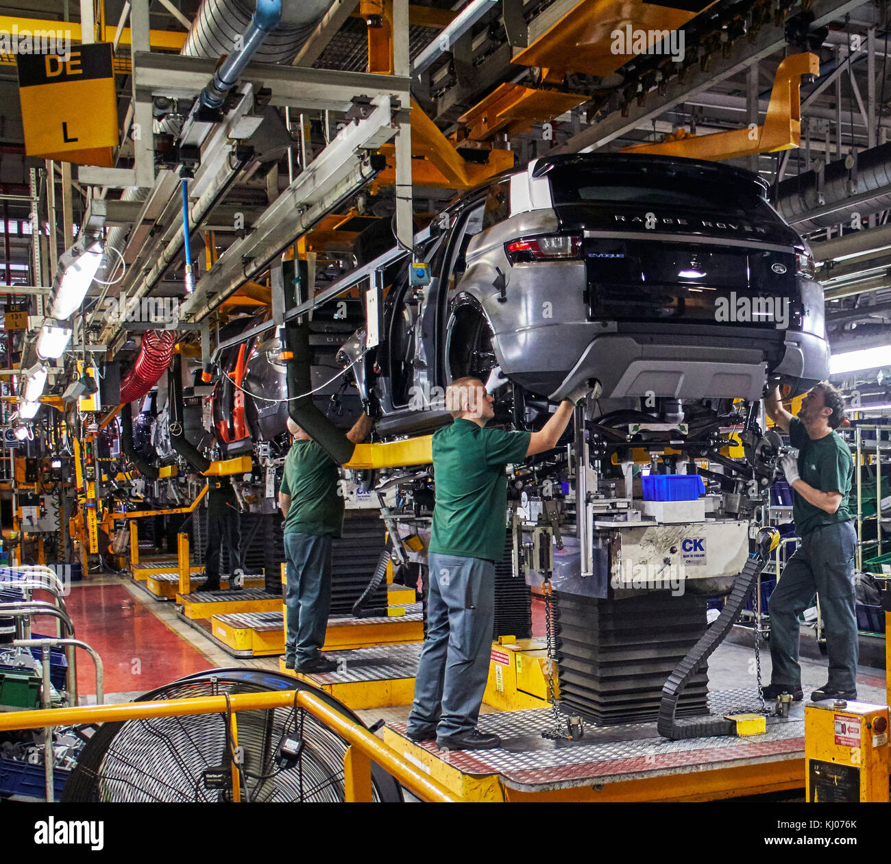 Workers on engine production line in car factory - Stock Image