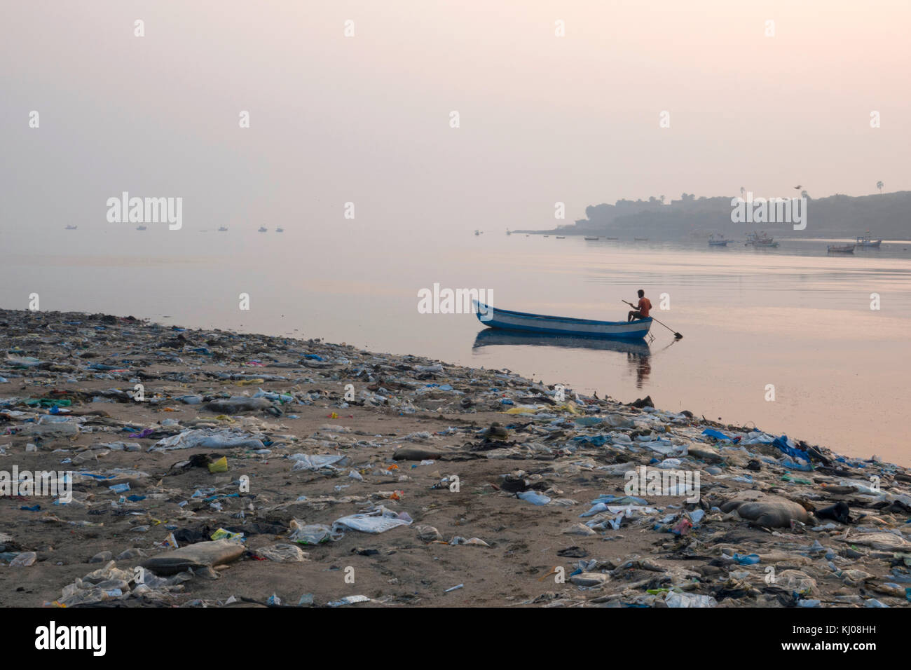 Fisherman paddles his boat past piles of plastic garbage and other rubbish on Versova Beach, Mumbai - Stock Image