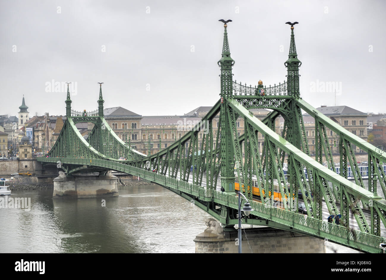 Liberty Bridge in Budapest, Hungary with a yellow tram crossing on a cloudy winter day. Stock Photo