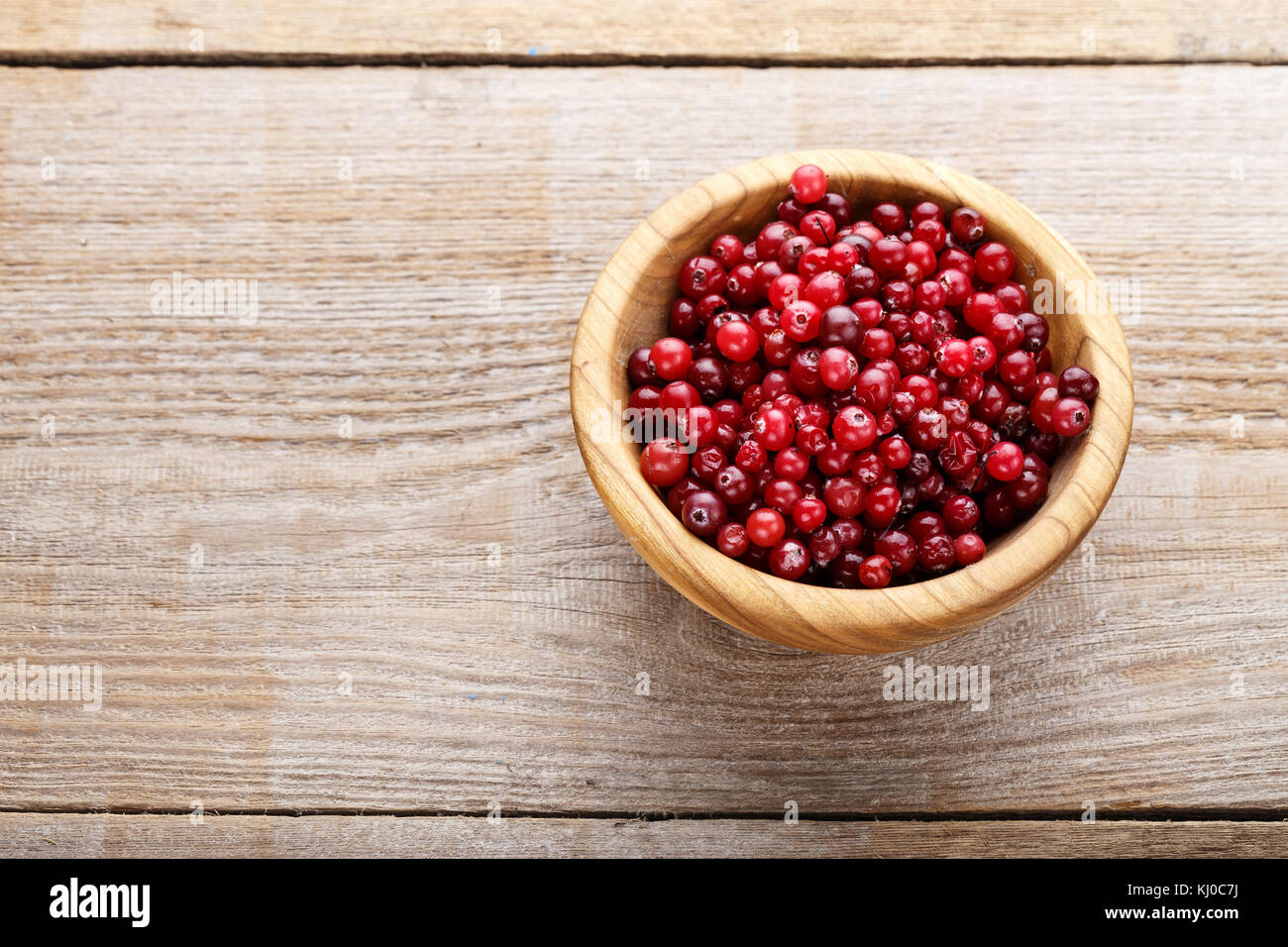 ripe cranberries in a plate, on a wooden background, organic vitamin product for strengthening immunity - Stock Image