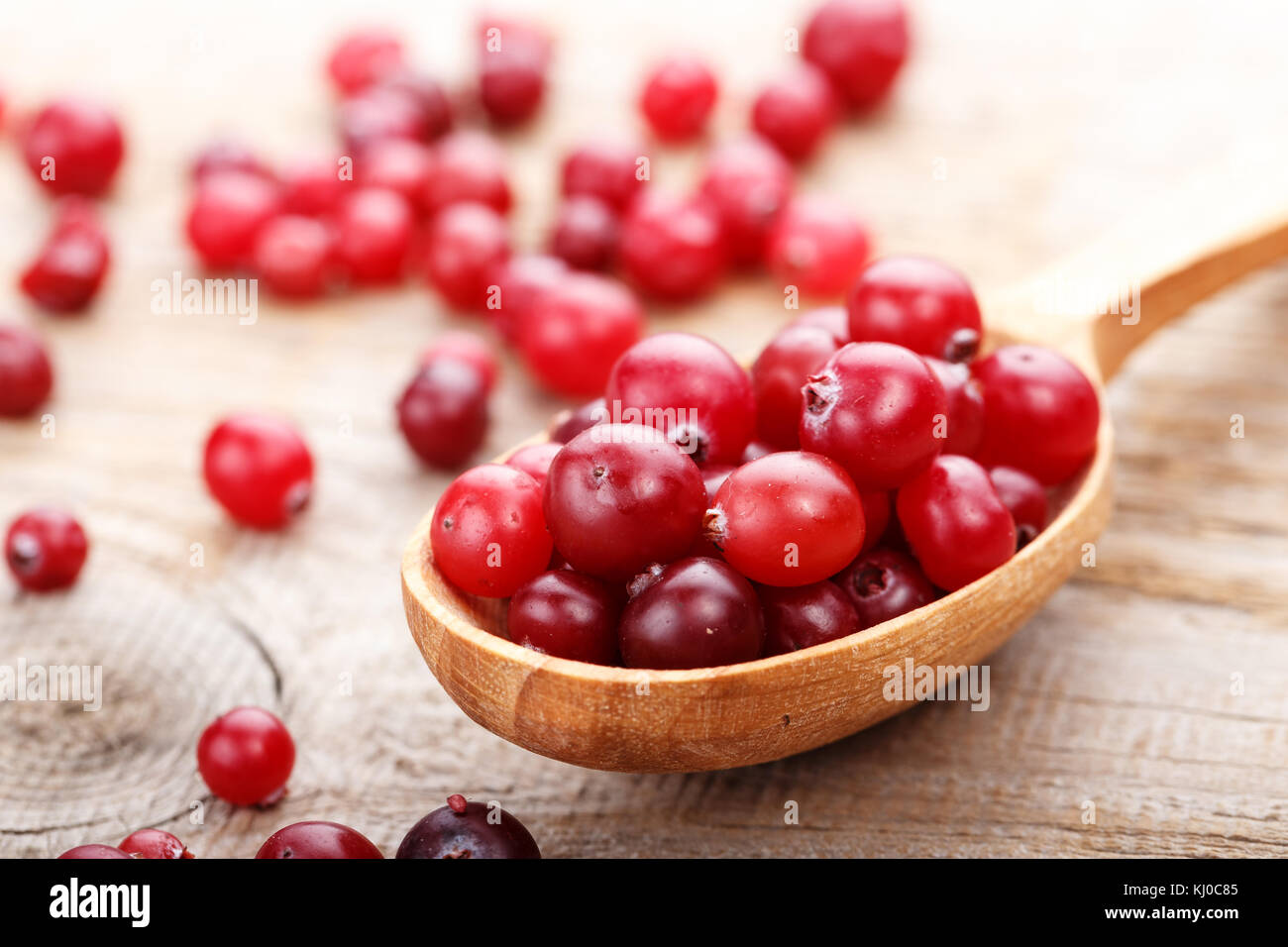 ripe cranberries on a wooden background, organic vitamin product for strengthening immunity - Stock Image