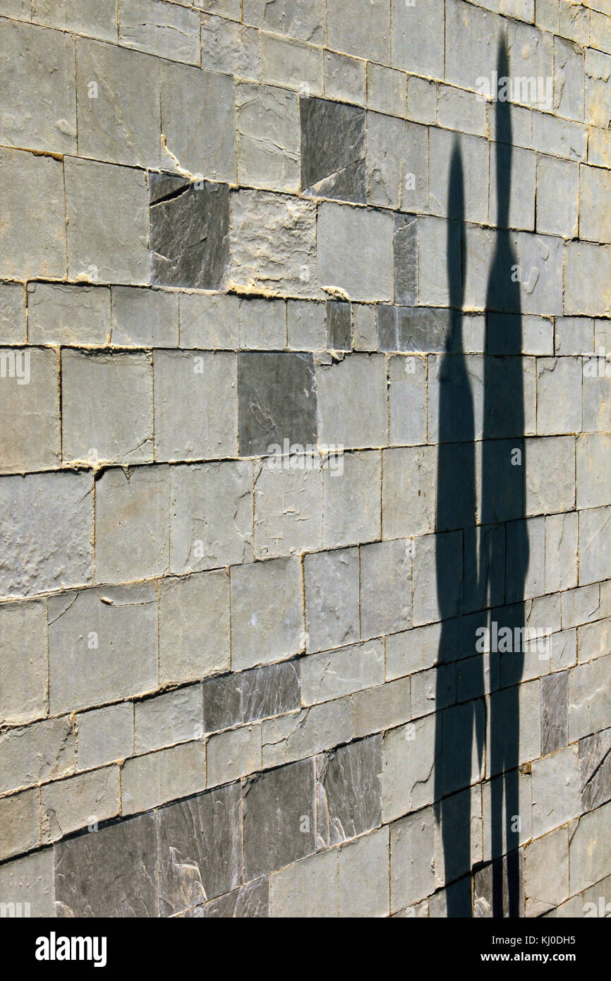 Shadow of two people silhouette projected on the stone wall - Stock Image