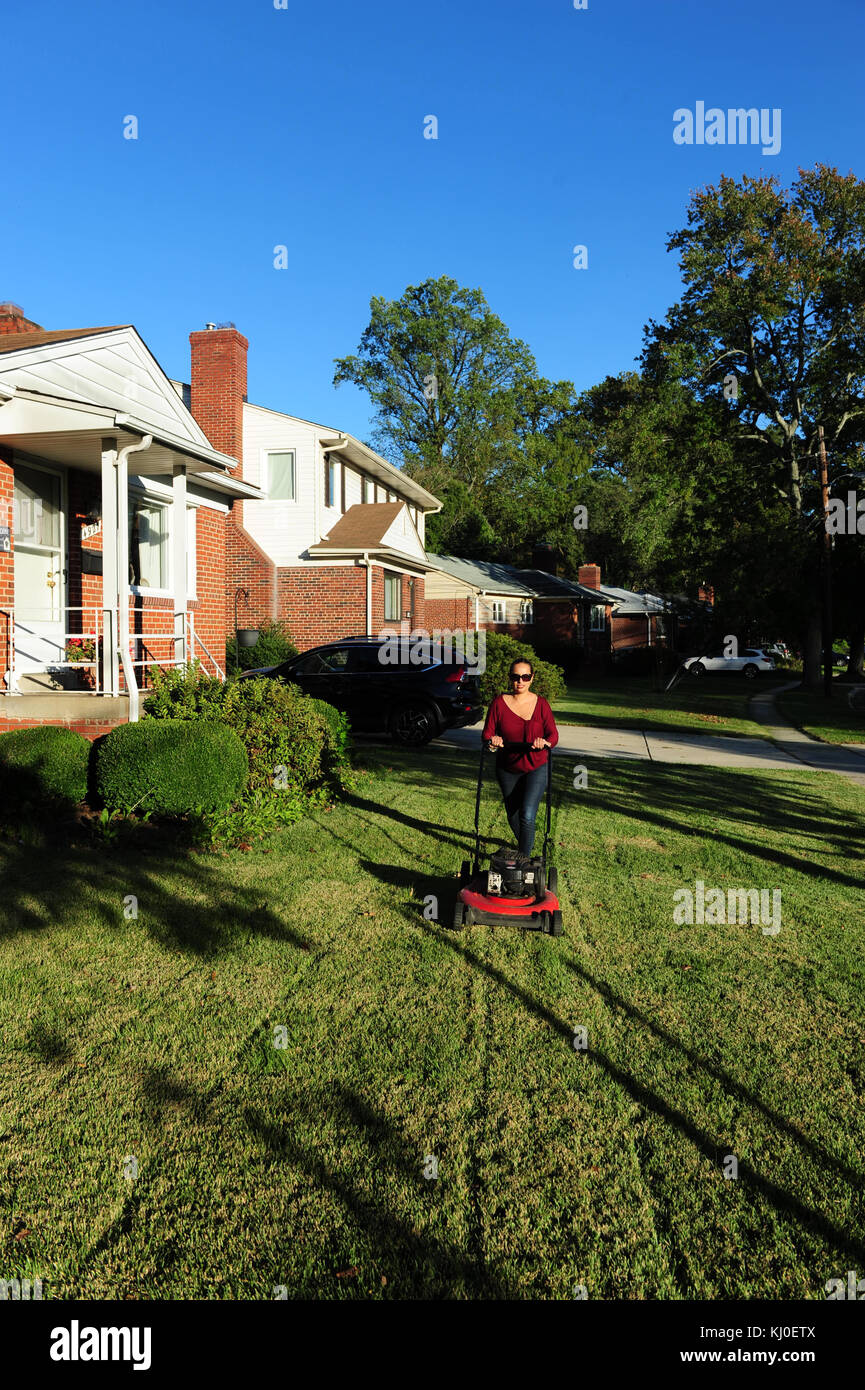 Hispanic woman mowing her lawn in suburban Maryland MD USA Garret Park - Stock Image