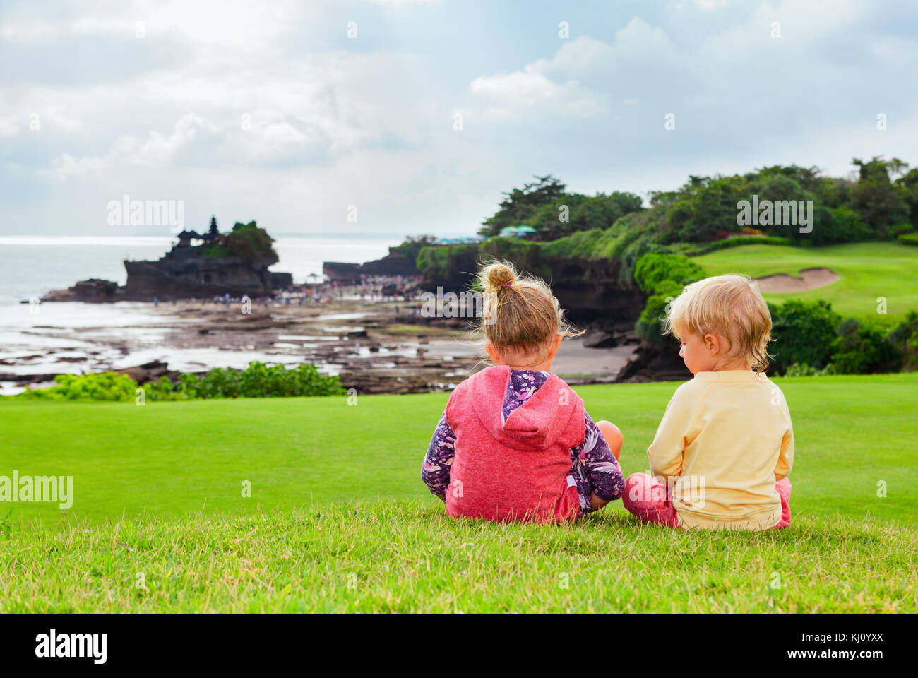 Happy kids at walk. Brother and sister sit on hill, look from high cliff at beach view, Balinese temple Tanah lot. - Stock Image