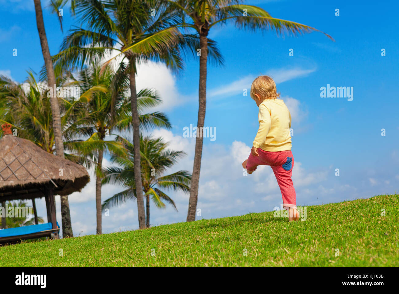 Happy child have fun at outside walk without parents. Active boy run and jump high by grass lawn in resort garden. - Stock Image