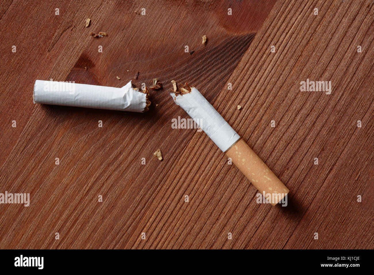 Broken cigarette closeup lying on wooden background - Stock Image