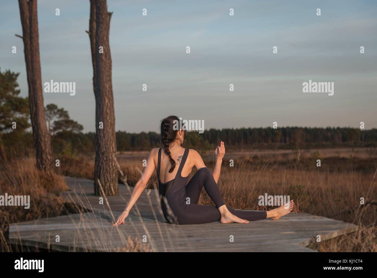 woman doing yoga, spinal twist yoga pose - Stock Image