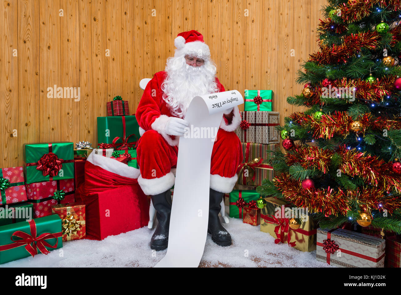 Santa Claus in his grotto surrounded by a Christmas tree with presents and gift wrapped boxes checking the Naughty - Stock Image