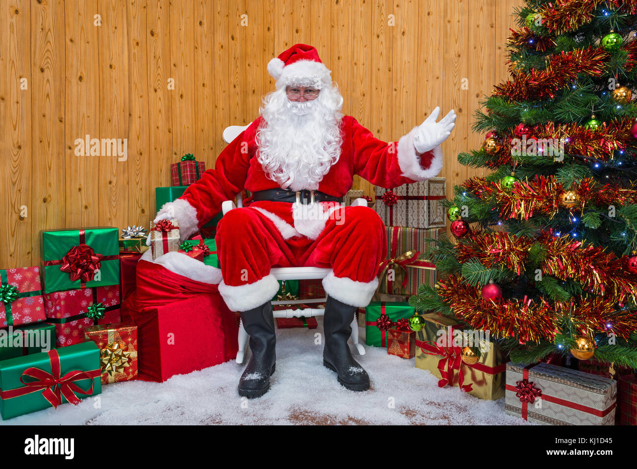 Santa Claus getting a gift wrapped present out of his sack as he welcomes you into his grotto. - Stock Image