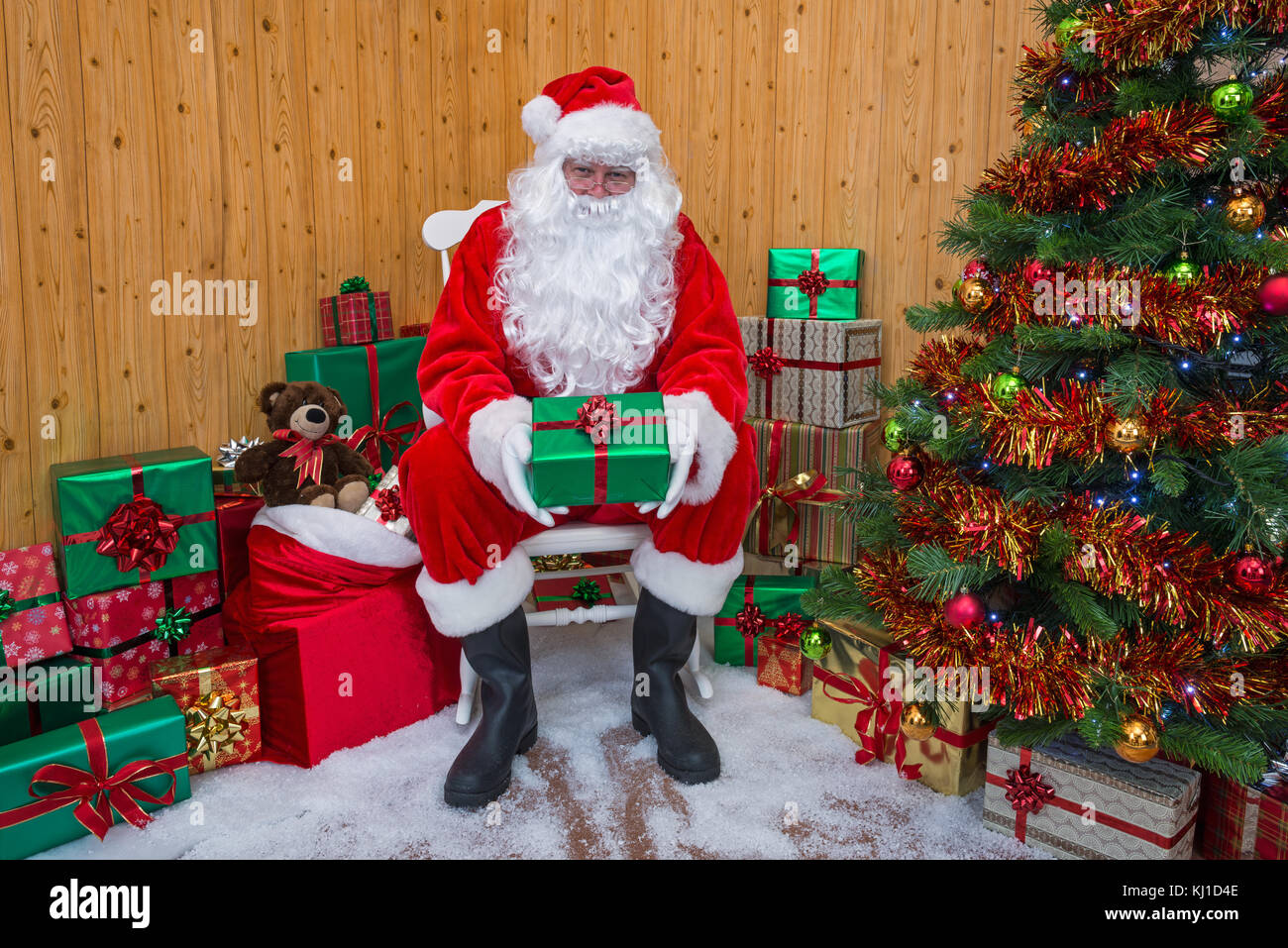 Santa Claus in his grotto surrounded by a Christmas tree with presents and gift wrapped boxes - Stock Image