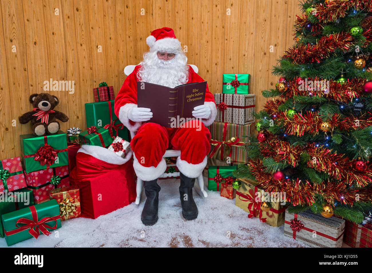 Santa Claus sitting in his grotto surrounded by a tree with presents and gift wrapped boxes whilst he reads his - Stock Image