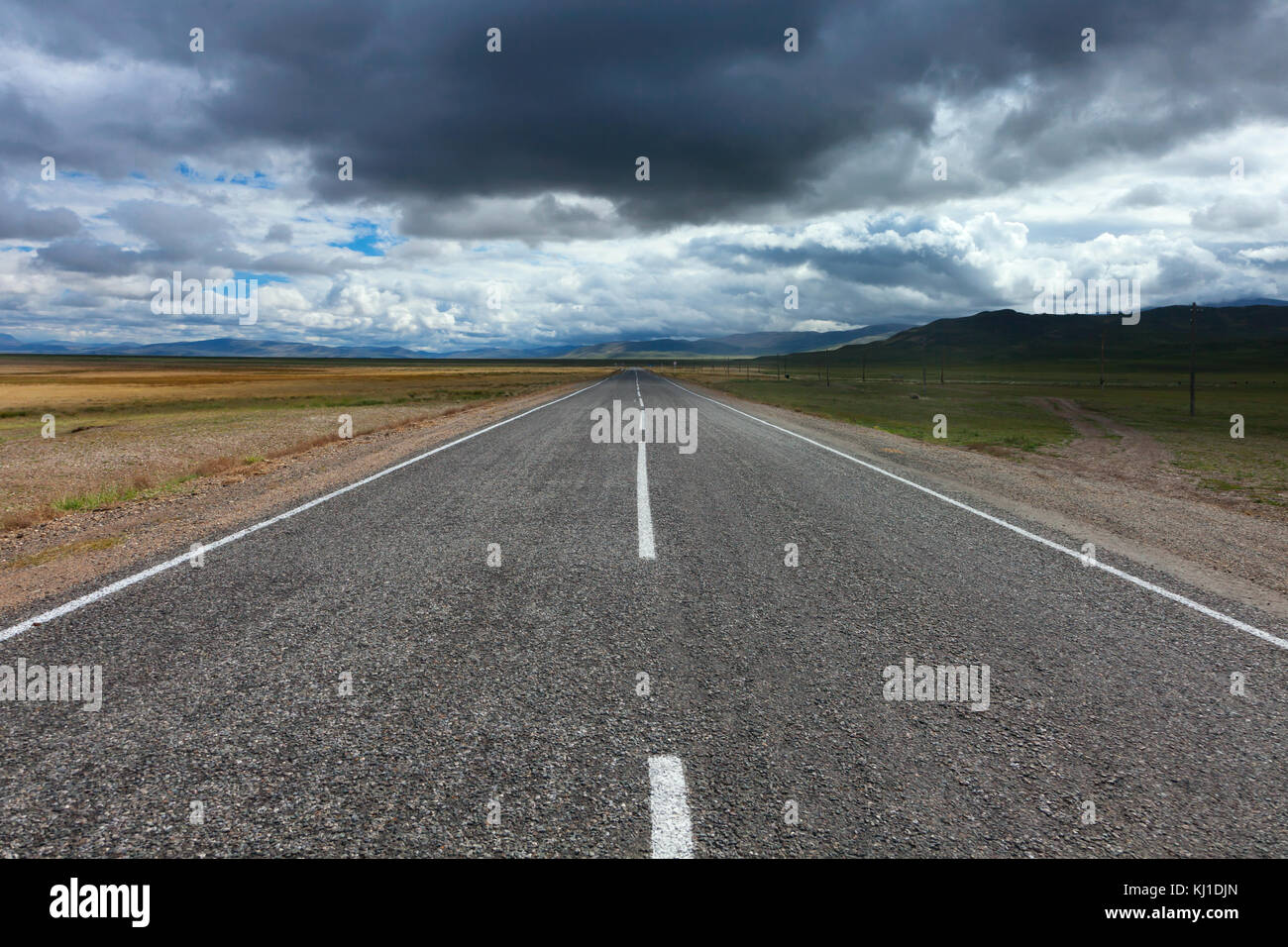 An empty desert road with dark and foreboding storm clouds on the horizon. - Stock Image