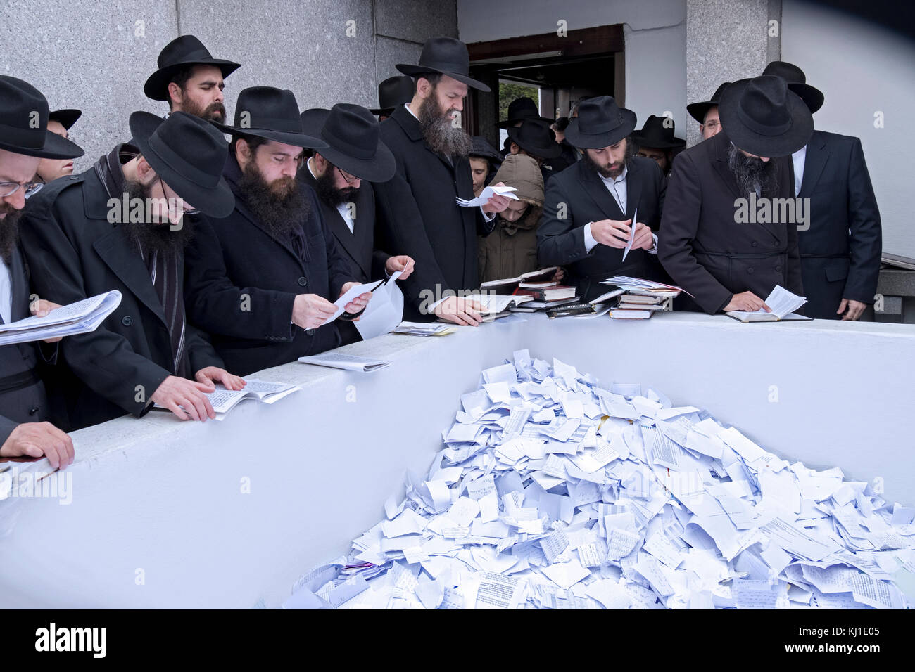 A group of religious Jewish man recite personal prayers at the site of the headstone of the Lubavitcher Rebbe, Menachem - Stock Image