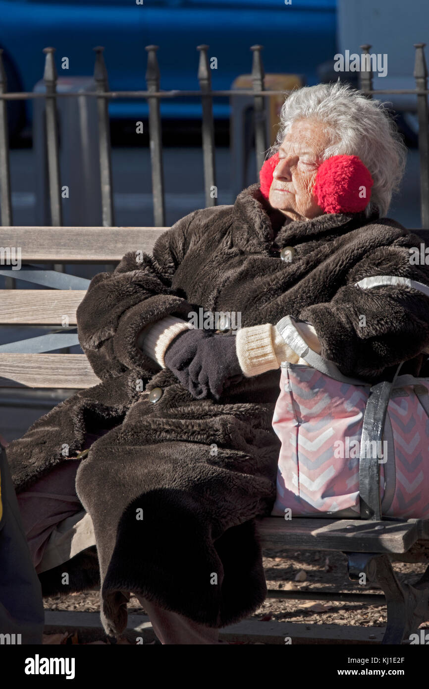 A senior citizen in a heavy coat sunning on a winter day in Father Demo Square in Greenwich Village, Manhattan, Stock Photo