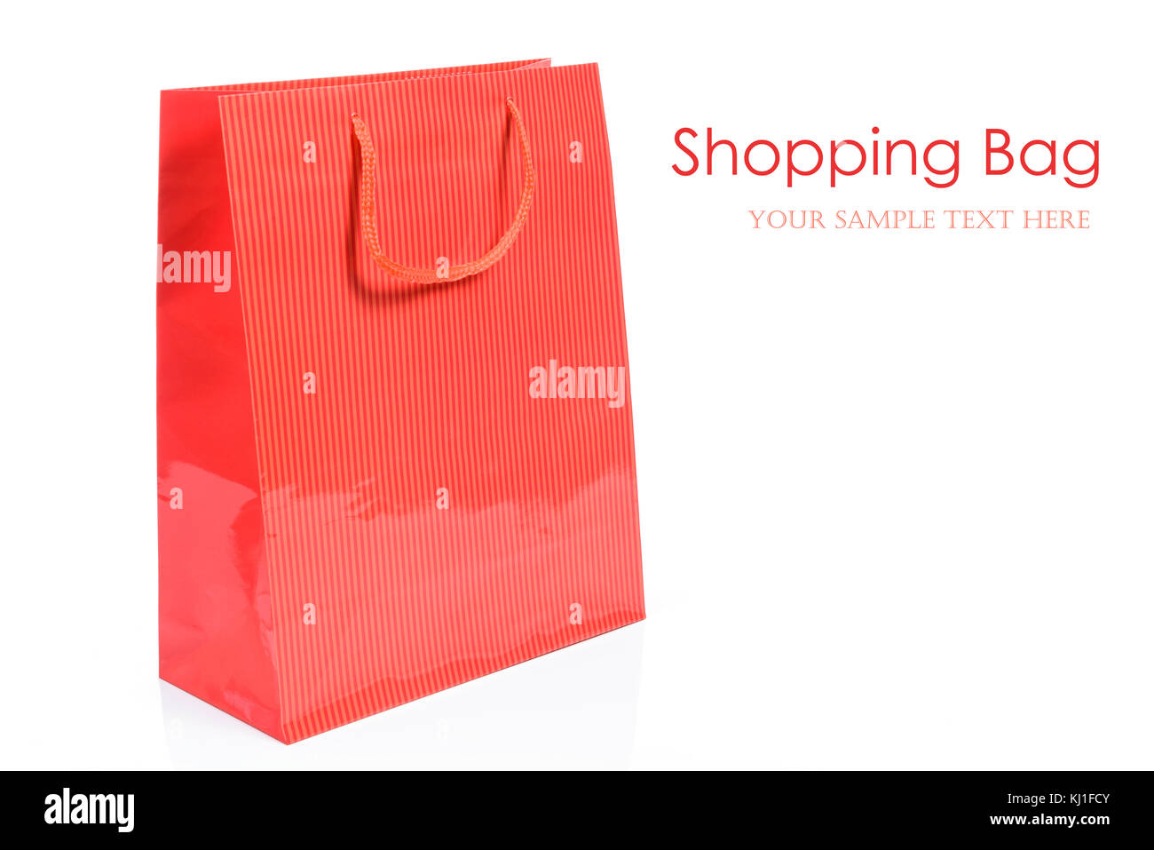 Luxury red shopping bag in close-up and isolated on a white background with copy space place (sample text). - Stock Image