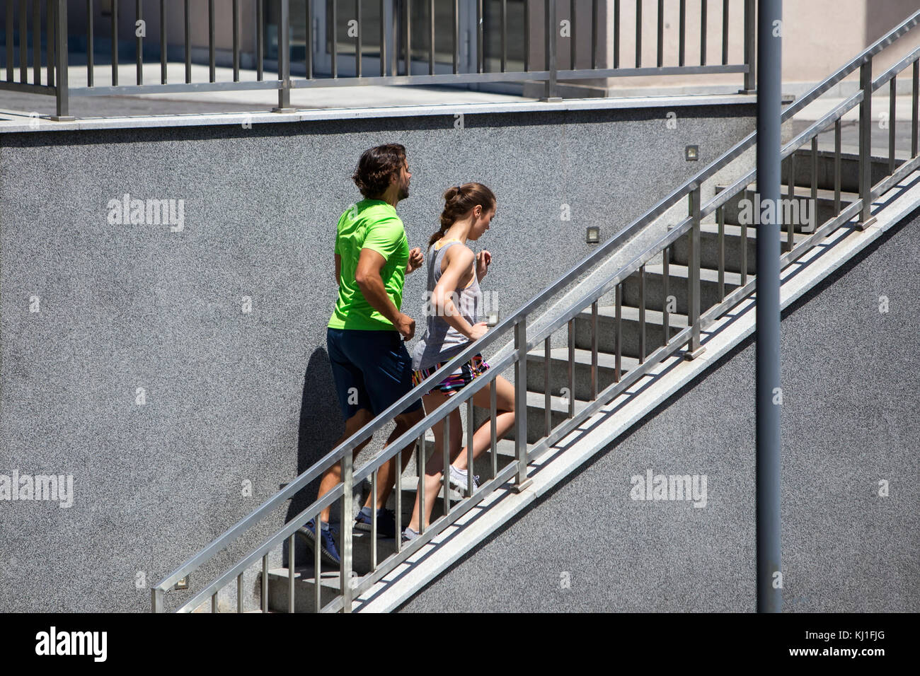 Young couple running upstairs in urban enviroment on summer day Stock Photo
