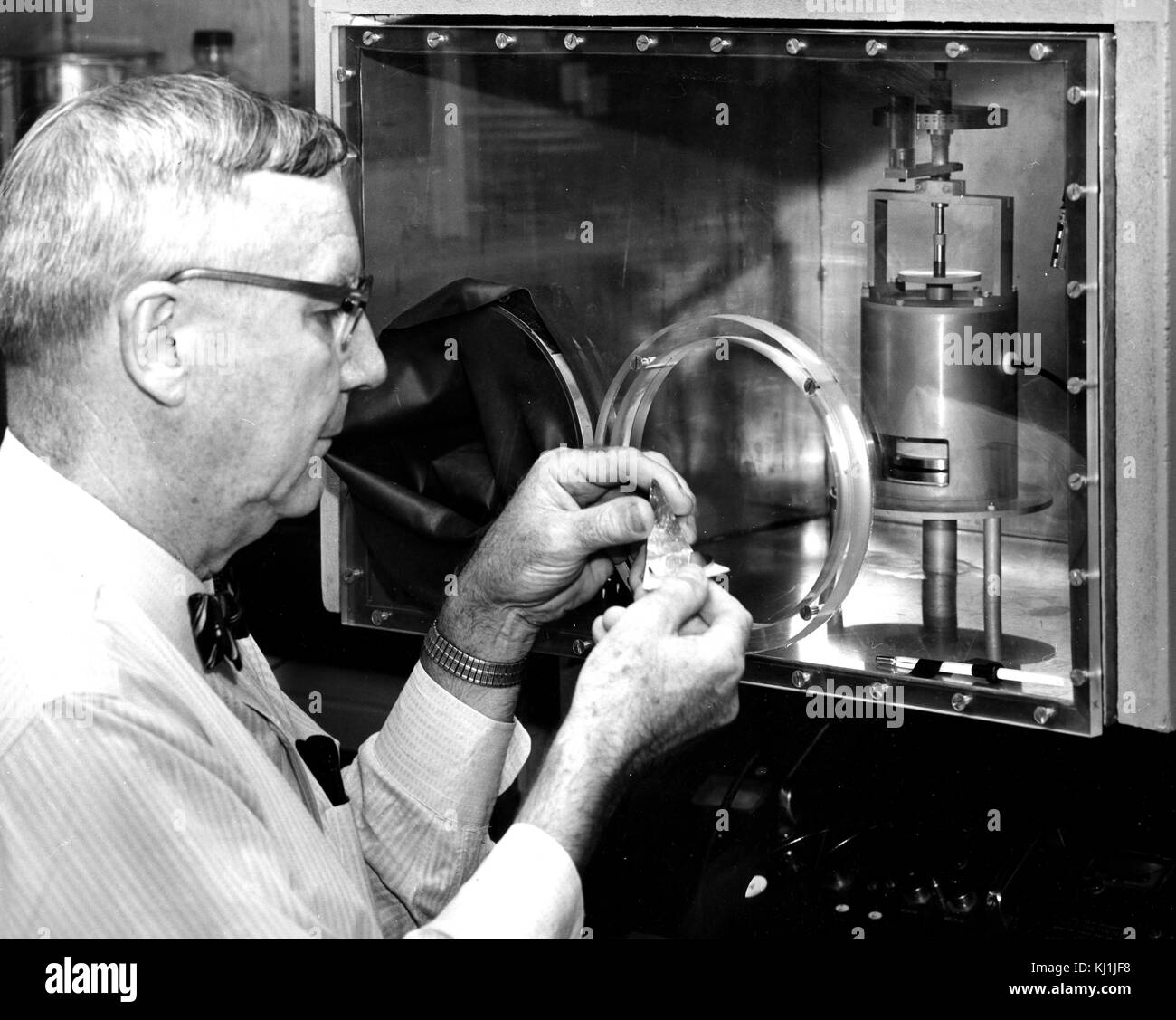 Photograph of a physicist monitoring a complex experiment using a closed respirometer. A respirometer is a general - Stock Image