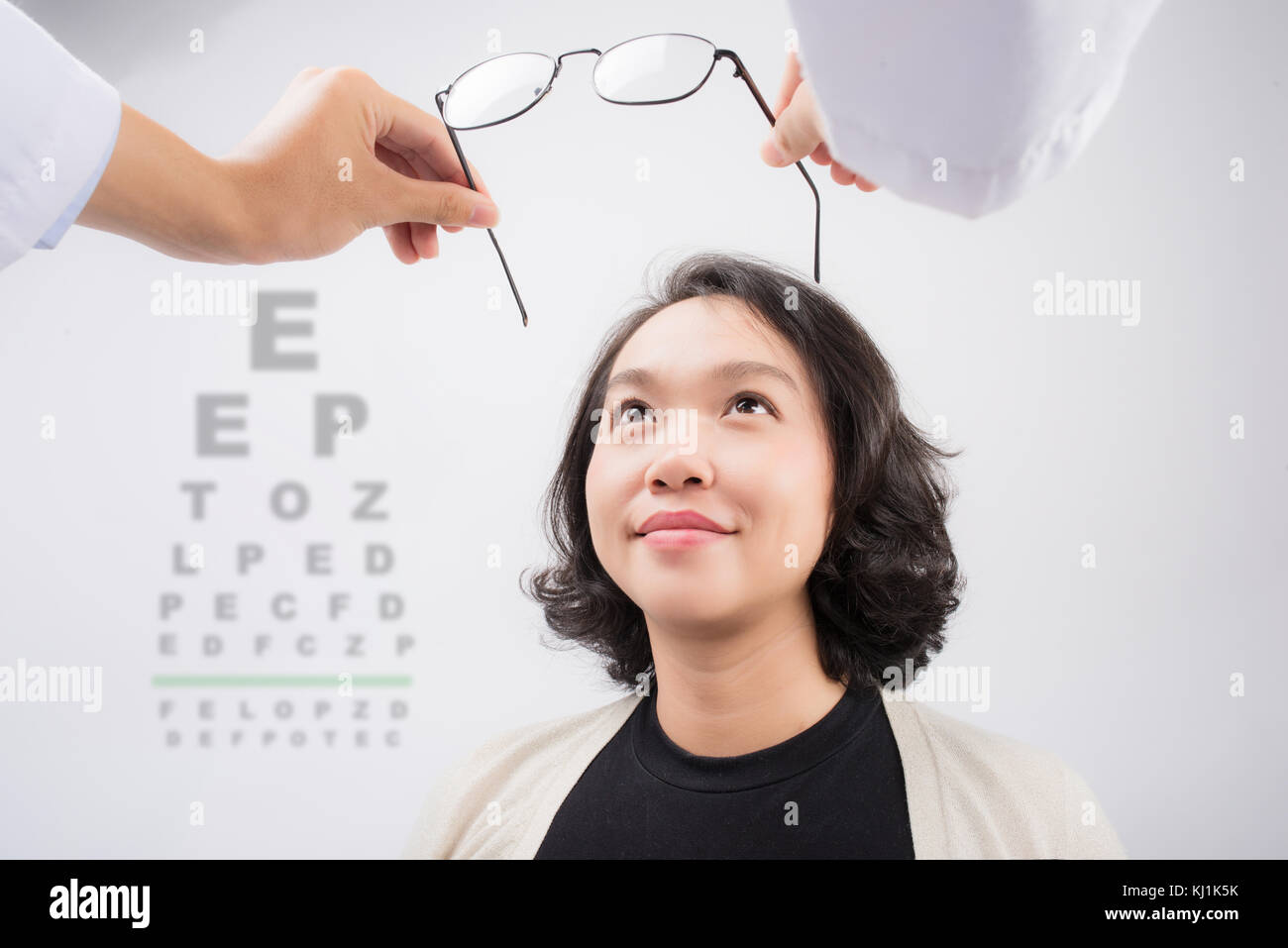 New glasses. Optometrist giving asian woman eyeglasses to try - Stock Image