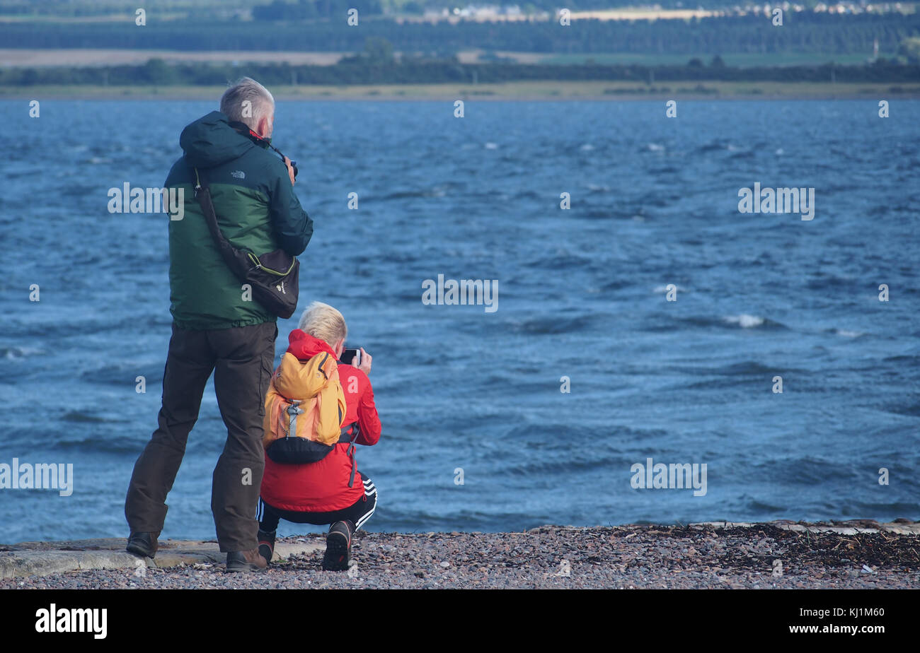 A couple photographing the sea at Cromarty Point, Scotlad - Stock Image