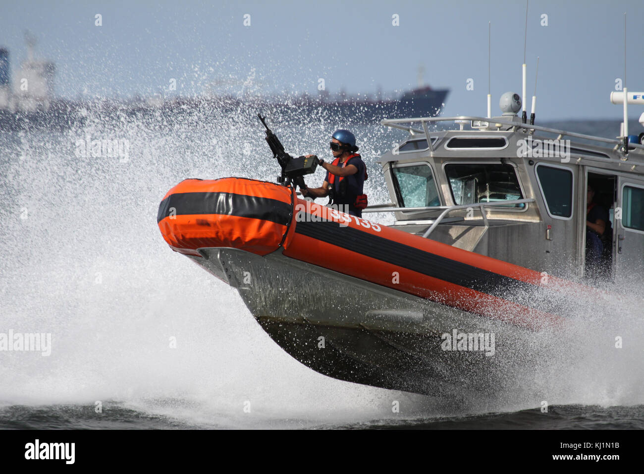 A machine gunning ICE agent stands ready as a patrol boat speeds patrol in the watrs off Miami, Florida - Stock Image