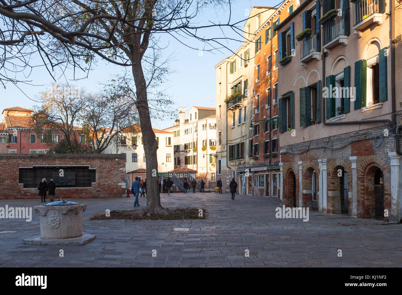 Ponte and Campo de Ghetto Novo at sunset, Cannaregio, Venice, Italy with people viewing the Holocaust wall and an - Stock Image