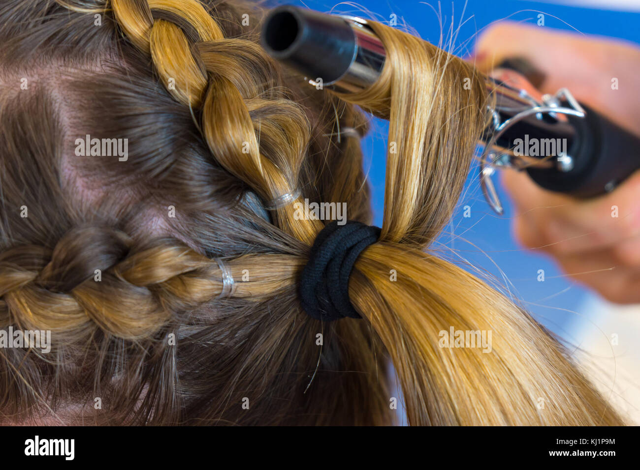 Stylist make curls hair - Stock Image