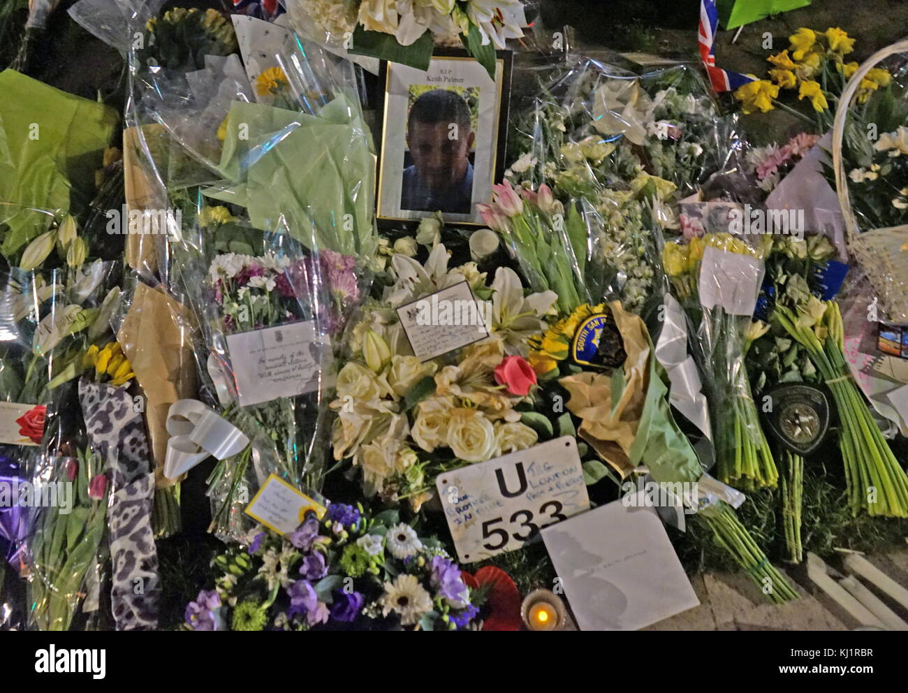 Flowers and tributes decorate a portrait of the murdered Police officer, PC Keith Palmer,, at Parliament green opposite - Stock Image